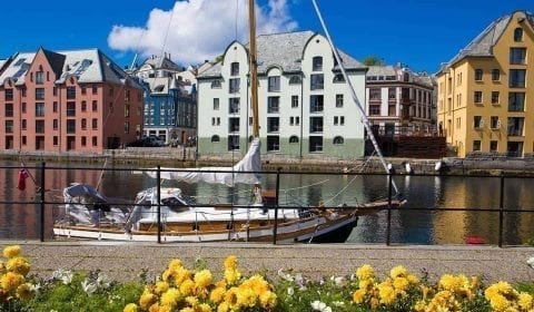 Sailboat docked on the Brosund canal, colourful Art Nouveau buildings on the waterside, Ålesund