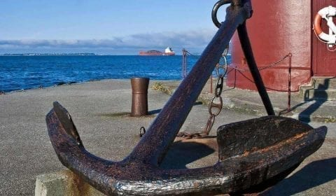 Grande ancora su un molo piccolo davanti ad un faro rosso nel centro di Ålesund