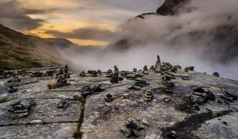 Blick über Steinhügel auf der Spitze der Trollstraße und Nebel im Tal