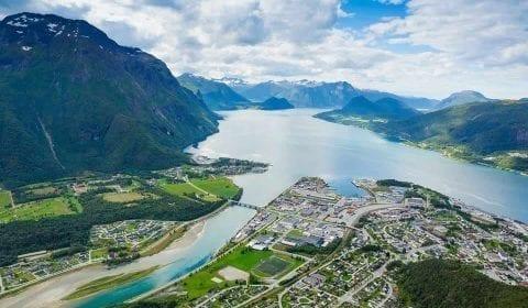 Vista panorámica de la ciudad de Åndalsnes, el río Rauma de color azul claro y el fiordo Romsdalsfjord, rodeado de montañas altas