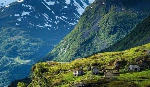 Casette di legno con erba sul tetto nelle montagne alte, neve sulle cime