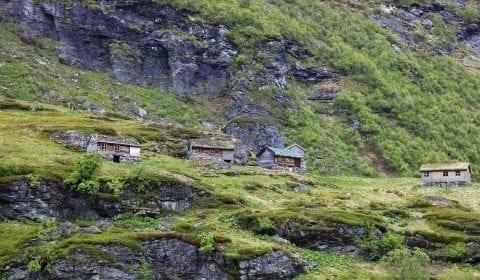 Casette di legno nelle montagne verdi a Geiranger