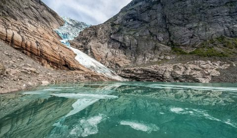 Clear blue glacier lake in front of the Briksdal Glacier, surrounded by mountains