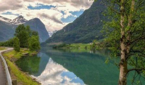 Idyllisch meer tussen de hoge bergen onderweg van Olden naar Geiranger