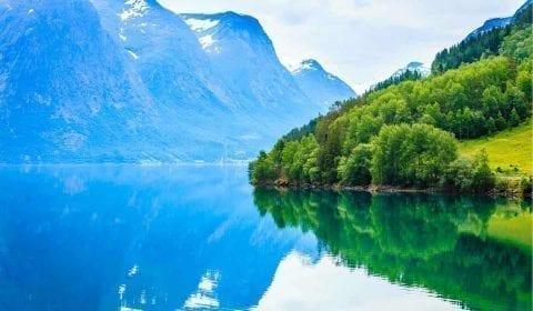 Een bergmeer omringd door hoge bergen bedekt met groene bomen