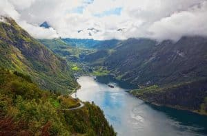 View from the Eagle Road, two cruise ships visiting the Geirangerfjord and Geiranger, mountains in the clouds
