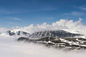 Vue du mont Dalsnibba sur le lac Djupvatn couvert sous les nuages, les sommets montagneux avec la neige dépassent des nuages