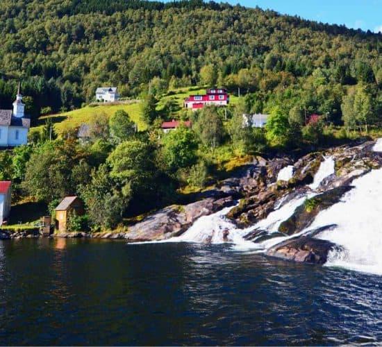 Cascada de Hellesylt que fluye de la montaña en el fiordo, casas e iglesia en la ladera de la montaña