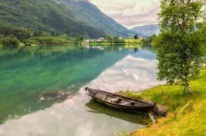 Bateau en bois abandonné sur la rive dans un lac de montagne turquoise à l'extérieur d'Olden