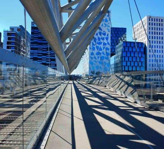 El acróbata, un puente peatonal, en el barrio del Código de Barras en Oslo, edificios modernos en el fondo
