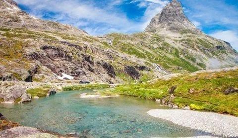 Klarblått vann strømmer i fjellene nært Trollstigen i Norge