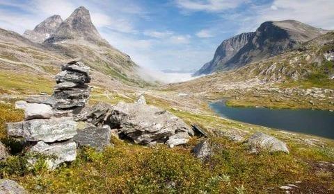 Ometto di pietra accanto a un prato verde a un piccolo lago nelle montagne alte vicino alla Strada dei Troll in Norvegia