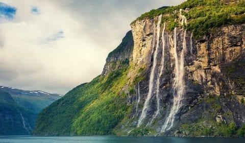 Syv Søstre foss kaster seg ned i Geirangerfjorden, grønne fjell, skyet himmel