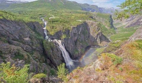 Arco iris en las gotas de la brillante cascada Voringsfossen en las verdes montañas