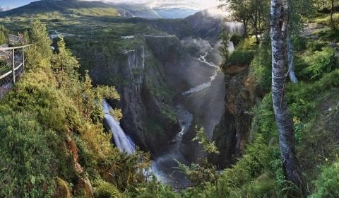 Vista de la cascada de Voringsfossen cayendo de la montaña en el valle verde de Mabodalen