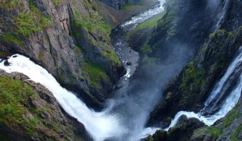 The impressive Voeringsfossen waterfall splashing from the mountain in the valley, Eidfjord, Norway