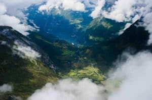 Mountains in the clouds, view from Mount Dalsnibba over the Geirangerfjord, the green valley and the village Geiranger