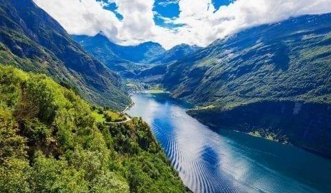 Panoramablick vom Aussichtspunkt der Adlerstraße über den UNESCO Geirangerfjord und das Dorf Geiranger, Norwegen