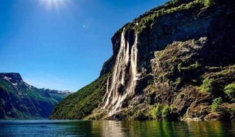 Der Sieben Schwestern Wasserfall unter einem klaren blauen Himmel, die Sonne scheint hell in Geiranger Norwegen