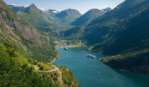 Høye grønne fjell omringer Geirangerfjorden hvor to skip ligger til kai, utsikt fra Ørnevegen