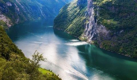 Fossen de Syv Søstre strømmer nedover en bratt fjellside mot den turkise Geirangerfjorden