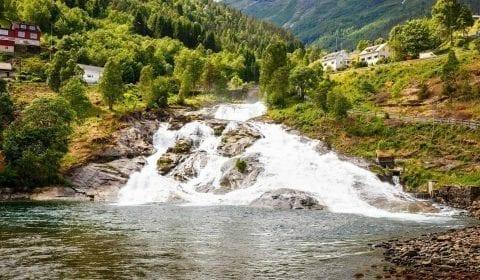 Waterval die over groene bergen naar beneden stroomt, houten huizen in Hellesylt, Noorwegen