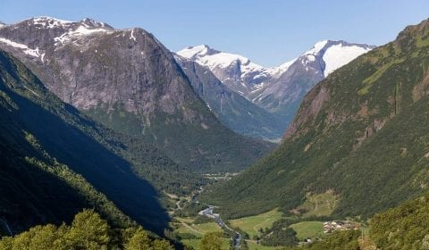 Aerial view over the green valley of Hjelle on the road from Hellesylt to Geiranger, snow on the peaks of the mountains on the sides of the valley