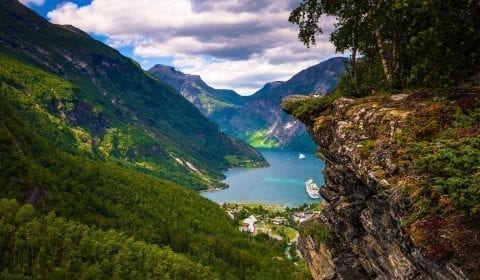Panoramic view from the gorge of Flydalsjuvet over UNESCO's Geirangerfjord, few clouds hanging over the green mountains