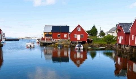 Røde og hvite trehus i fiskeværet Bud nært Atlanterhavsveien i Norge