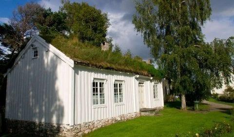 Een wit houten huis met gras op het dak en een groene tuin in Molde, Noorwegen