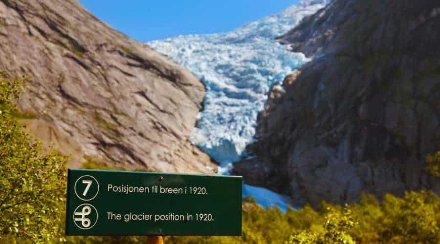 Schild mit dem Endpunkt des Gletschers 1920 mit dem aktuellen Briksdal-Gletscher, umgeben von Bergen im Hintergrund, Olden, Norwegen
