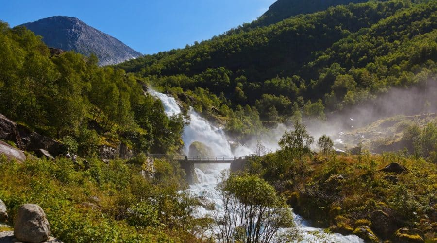 The spectacular Kleivafossen waterfall splashing down from a mountain next to the hiking trail towards the Birksdal glacier in Olden, Norway
