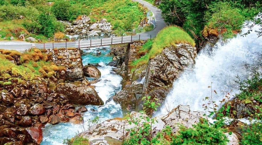 Frisches und klares blaues Wasser aus dem Wasserfall Kleivafossen, der unter einer Brücke in Olden, Norwegen, fließt
