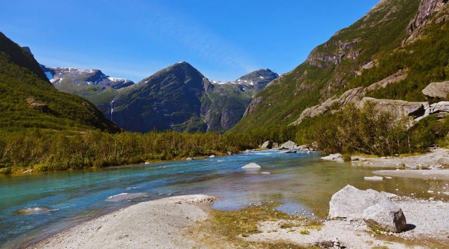 Helder blauw water van de Briksdal Gletsjer stroomt tussen de groene bergen door, Olden, Noorwegen