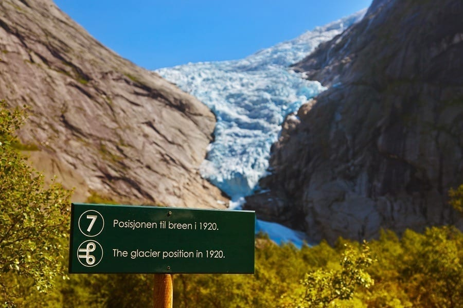 A trail marker on the hike to the Briksdal glacier with a view of the glacier in the background