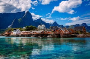 Rorbu cabins over crystal blue waters in Lofoten, Norway with dramatic mountains in the background
