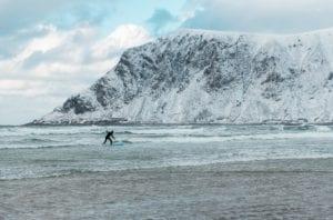 A surfer surfs in the waters of Lofoten, Norway