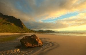A view of the midnight sun over a sandy beach in , Lofoten, Norway.